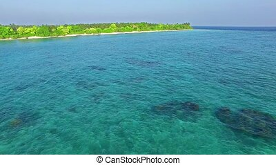 Flying over water, stone and sand beach in the Maldives Thoddoo.
