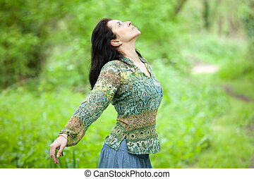 woman in forest - brunette woman breathing in verdant spring...