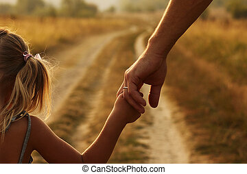 the parent holds the hand of a small child - a the parent...