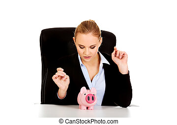 Happy business woman with a piggybank behind the desk.