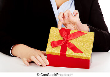 Business woman opens a gift box behind the desk