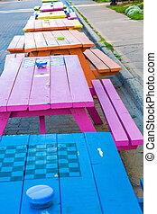 Blue Pink and Orange Picnic Tables - A line of colorful...