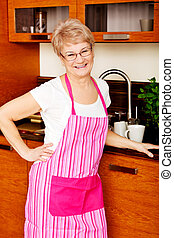 Happy senior woman standing in kitchen