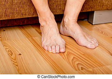 Feet of old woman on the floor.