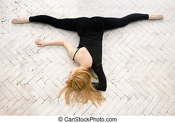 Young attractive female fitness woman performing a twine -...