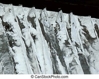 Icicles. Spring. - Icicles hanging from a roof against the...