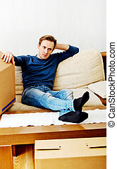 Tired man sitting on couch with cardboard boxes around