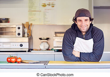 Friendly entrepeneur in his clean takeaway food stall -...