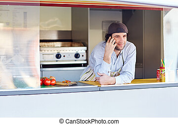 Entrepeneur talking on the phone at his food business place...