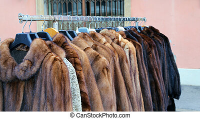 many fur coat for sale in the flea market outdoors -...