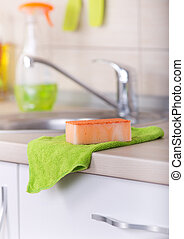 Dishwashing tool on kitchen countertop - Close up of orange...
