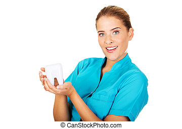 Young female dentist holding tooth model.