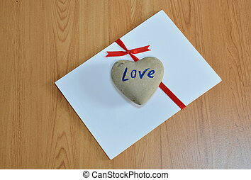 heart stone on white paper tie red ribbon
