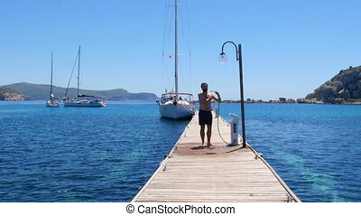 happy man showering on wooden pier at beach after swimming