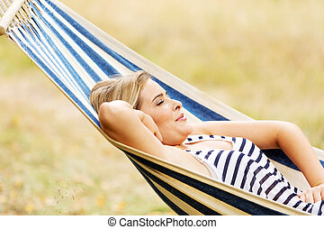 Young blonde woman resting on hammock
