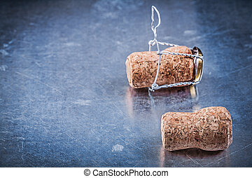 Champagne corks with twisted wires on metallic background