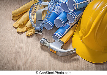 Protective workwear rolled blueprints claw hammer on wooden...