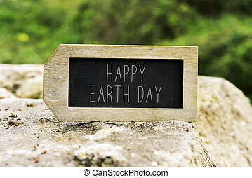 chalkboard with the text happy earth day - closeup of a...