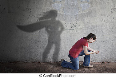 Superhero Shadow - A woman prays while her shadow is a...