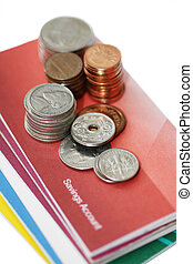 Savings - Some coins on savings account passbook.