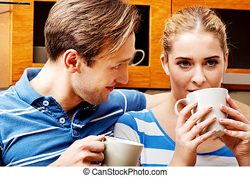 Young couple drinking coffee or tea in kitchen