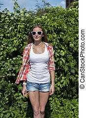 Bright sexy, beautiful young girl, wearing glasses posing in front of a green garden bushes,