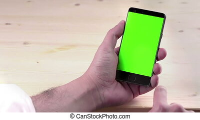 man hand using a smart phone with chroma key on wood...