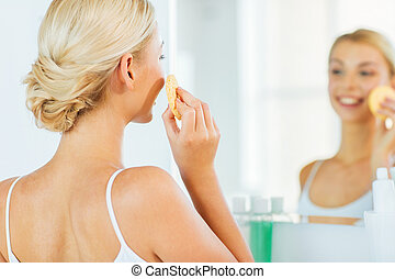 close up of woman washing face with sponge at home