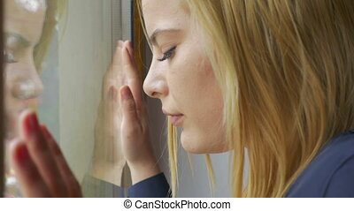 Young sad woman looking out the window