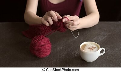 Woman knitting and drinking coffee - Woman knitting red yarn...