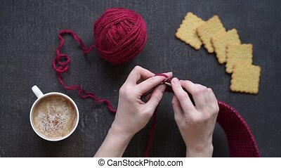 Woman knitting while drinking coffee with crackers over a...