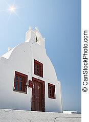 Oia Village Church with sunflare - A view of the white...
