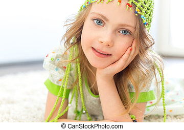 Cute girl green hat white carpet - Cute girl wearing a green...