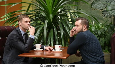businessman waiting. evinces impatience. knocking fingers. colleague talking on the phone