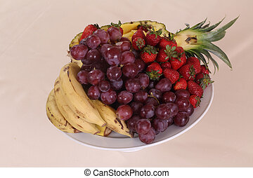 grapes, pineapple, bananas and fresh strawberries on the...