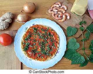 Cooking pizza with shrimps, nettles, tomato, onion, cheese...