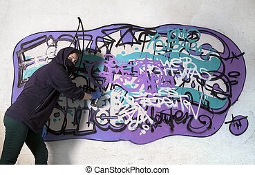 Young girl tagging wall with graffiti, enjoyment