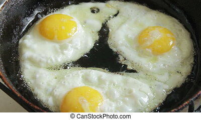 Scrambled Eggs Fried in a Pan - Three fried eggs fried in a...
