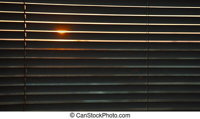 the sun's rays breaking through the closed shutters,...