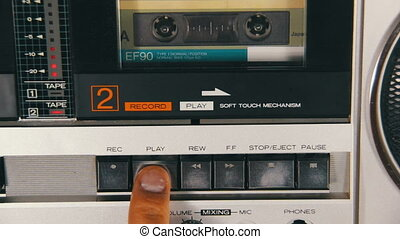 Pushing a Finger Play and Stop Button on a Tape Recorder