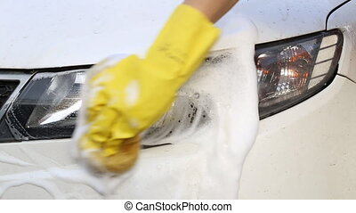 Rinsing all the soap suds off of a car.