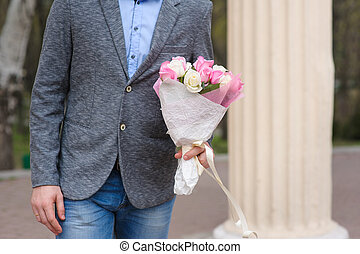 Man with bouquet of flowers waiting for a woman