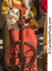 Woman working on old spinning wheel - Woman spinning on...