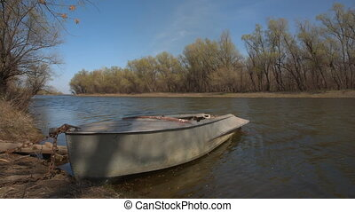 Boat at the riverside - Old fishing boat at the river side,...
