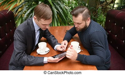Two men at a cafe using a Tablet PC
