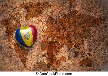 heart with national flag of moldova on a vintage world map...