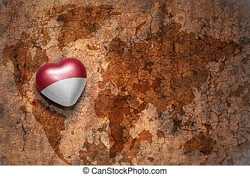 heart with national flag of monaco on a vintage world map...