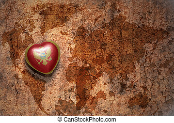heart with national flag of montenegro on a vintage world...