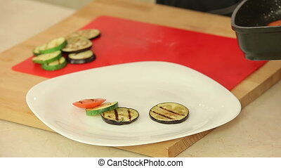 Grilled vegetables on a plate - Chef is putting grilled...