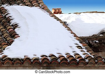 aged clay roof tiles snowed under winter snow - aged clay...